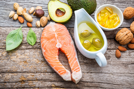 Selection food sources of omega 3 and unsaturated fats. Superfood high vitamin e and dietary fiber for healthy food. Almond,pecan,hazelnuts,walnuts,olive oil,fish oil and salmon on wooden background. Stock Photo