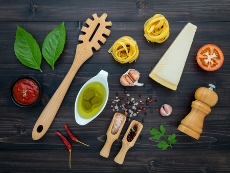 The  pasta on black wooden background. Yellow italian pasta with ingredients. Italian food and menu concept. Фото со стока
