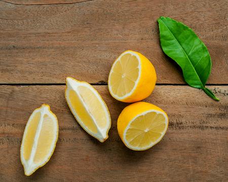 Fresh lemons and  lemons leaves on rustic wooden