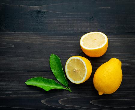 Fresh lemons and  lemons leaves on dark wooden