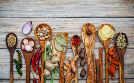 Various of spices and herbs in wooden spoons.