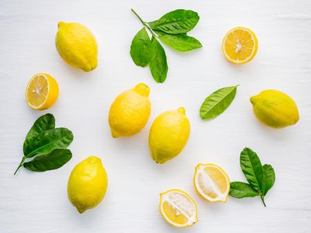 Fresh lemons and  lemons leaves on white wooden Imagens