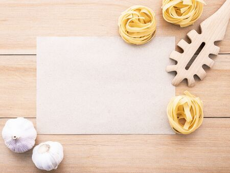 Italian foods concept and menu design . Blank paper and  pasta ladle on wooden Фото со стока