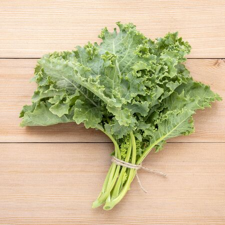 Fresh organic curly kale leaves flat lay on a wooden table with copy space. Stock Photo