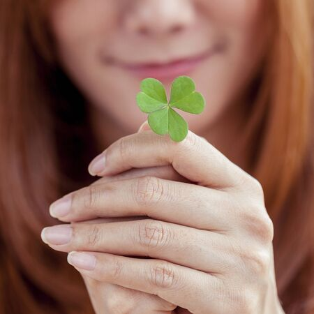The girl hold  Clover leaf . Concept for love , hope and goodness.
