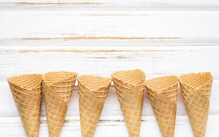 Flat lay ice cream cones collection on white wooden