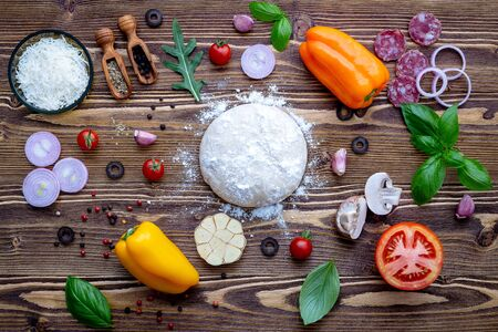 Raw dough with ingredients for homemade pizza on shabby wooden Imagens