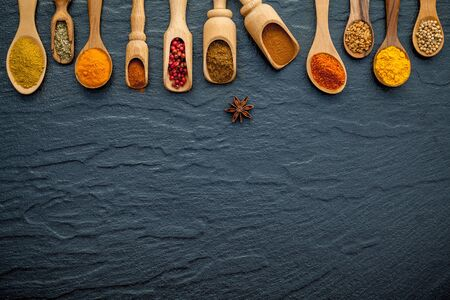 Various of Indian spices and herbs in wooden spoons.