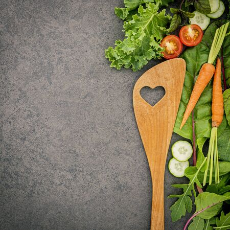 Wooden spoon and vegetables on dark stone Imagens
