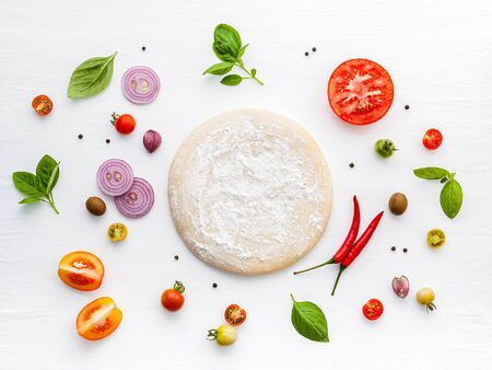 The ingredients for homemade pizza on white wooden