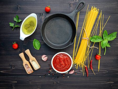 The thin spaghetti on black wooden background. Yellow italian pasta with ingredients. Imagens