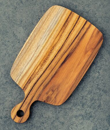Chopping teak wood cutting board on dark stone