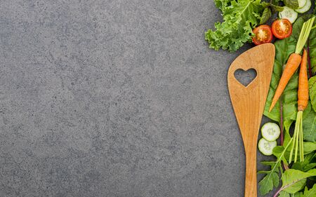 Wooden spoon and vegetables on dark stone Stock Photo