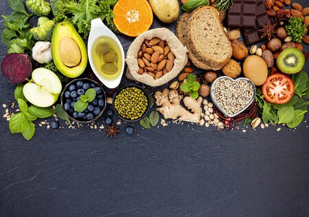 Ingredients for the healthy foods selection. The concept of healthy food set up on dark stone background. Stock Photo