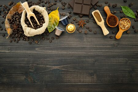 Coffee beans, coffee capsule and coffee powder on dark wooden