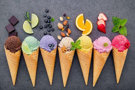Varios de sabor a helado en conos de arándano, lima, pistacho, almendra, naranja, chocolate, vainilla y café sobre fondo de piedra oscura. Concepto de menú de verano y dulces.