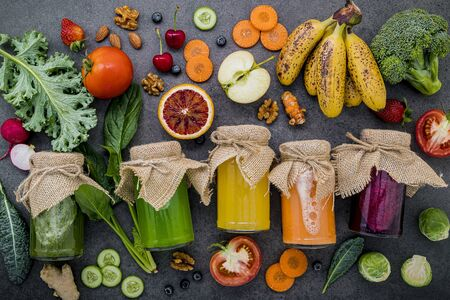 Colourful healthy smoothies and juices in bottles with fresh tropical fruit and superfoods on dark stone background with copy space.
