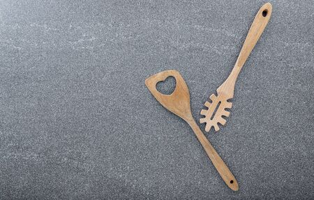 Pasta noodle spoon , Pasta scoop ladle  and  spatula on dark granite background with copy space.