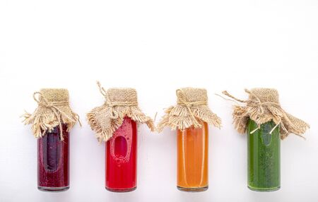 Colourful healthy smoothies and juices in bottles on white background with copy space. Zdjęcie Seryjne