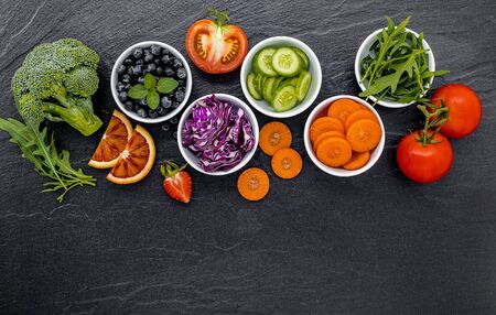 Colourful ingredients for healthy smoothies and juices on dark stone background with copy space. Zdjęcie Seryjne