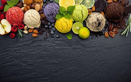 Varias bolas de sabor a helado de arándano, lima, pistacho, almendra, naranja, chocolate y vainilla sobre fondo de piedra oscura. Concepto de menú de verano y dulces. Foto de archivo