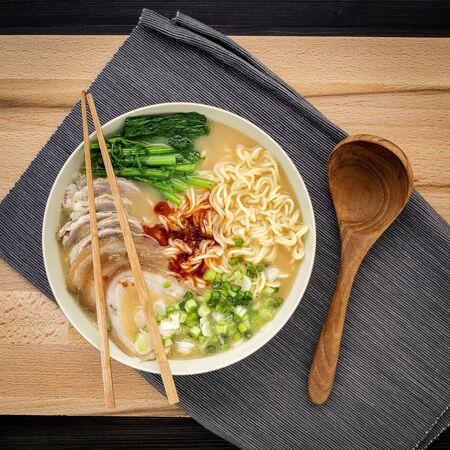 Asian ramen noodle pork bone based soup with pork chashu on cutting board background.