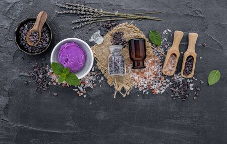 Himalayan black salt and Himalayan pink salt with peppermint and lavender flower on dark concrete background. Himalayan salt commonly used in cooking and for bath products such as bath salts.