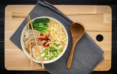 Asian ramen noodle pork bone based soup with pork chashu on cutting board background.
