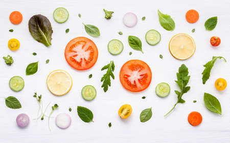 Food pattern with raw ingredients of salad, lettuce leaves, cucumbers, tomatoes, carrots, broccoli, basil ,onion and lemon flat lay on white wooden background. Standard-Bild