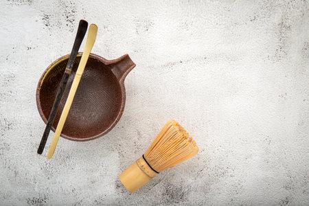 Matcha set bamboo matcha whisk and chashaku tea scoop,matcha ceramic bowl set up on white concrete background. Reklamní fotografie