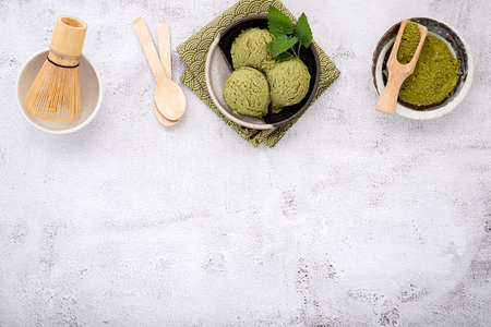 Matcha green tea ice cream with waffle cone and mint leaves  setup on white stone background . Summer and Sweet menu concept.
