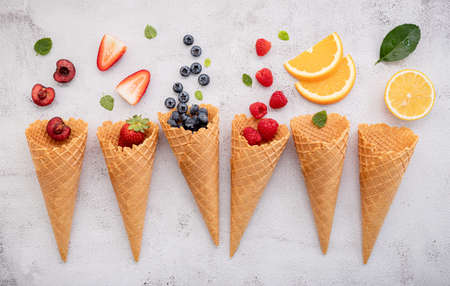 Various of ice cream flavor in cones blueberry ,strawberry ,pistachio ,almond ,orange and cherry setup on concrete background . Summer and Sweet menu concept.