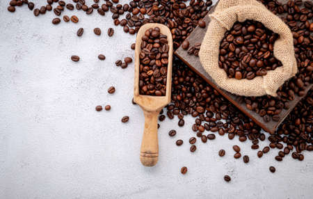 Roasted coffee beans with scoops setup on white concrete background.