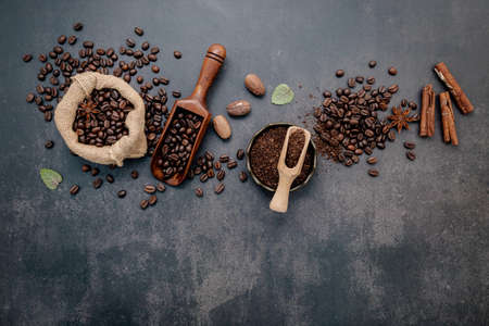 Coffee background with various of roasted coffee beans and flavourful ingredients for make tasty coffee setup on dark stone background.