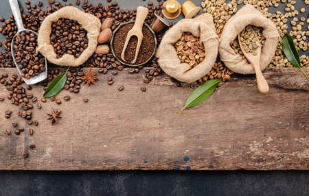 Background of various coffee , dark roasted coffee beans , ground and capsules with scoops setup on wooden background with copy space.