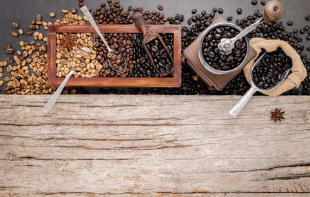 Various of roasted coffee beans in wooden box with manual coffee grinder setup on shabby wooden background. Standard-Bild