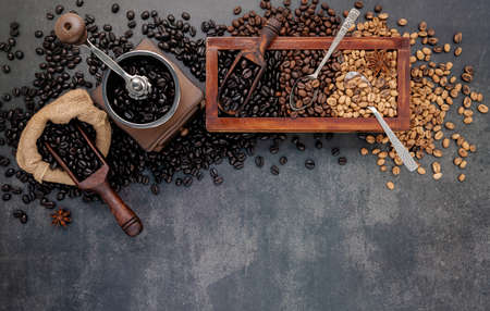 Various of roasted coffee beans in wooden box with manual coffee grinder setup on dark stone background.