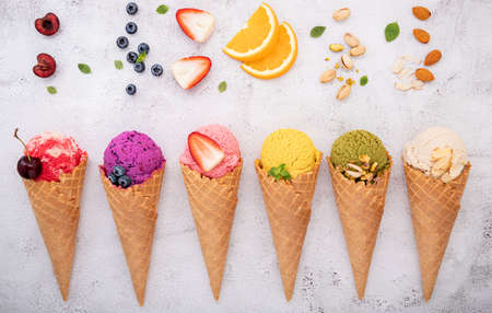 Various of ice cream flavor in cones blueberry ,pistachio ,almond ,orange and cherry setup on white stone background . Summer and Sweet menu concept.