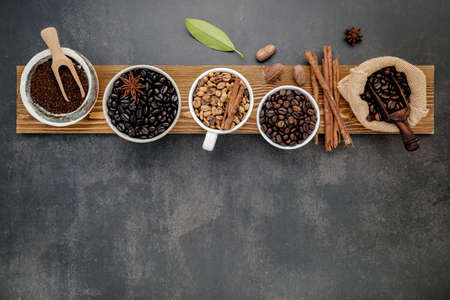 Brown unroasted and dark roasted coffee beans in coffee cup with scoops setup on dark stone background.