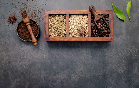 Green and brown unroasted and dark roasted coffee beans in wooden box with scoops setup on dark concrete background.