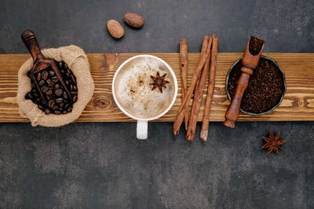 Cup of coffee and roasted coffee beans ,coffee powder and flavourful ingredients for make tasty coffee setup on dark stone background.