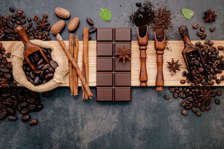 Roasted coffee beans with coffee powder and flavourful ingredients for make tasty coffee setup on dark stone background.
