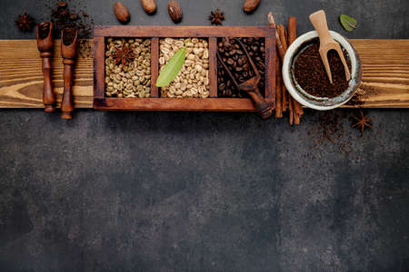 Green and brown unroasted and dark roasted coffee beans in wooden box with scoops setup on dark stone background. Standard-Bild