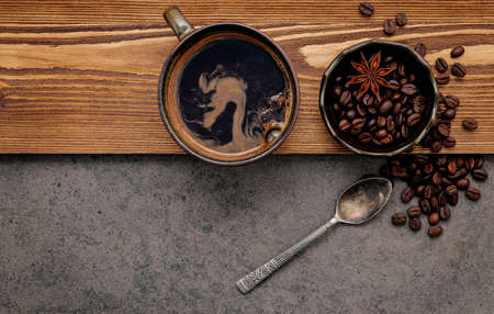 Roasted coffee beans with coffee cup setup on dark stone background.