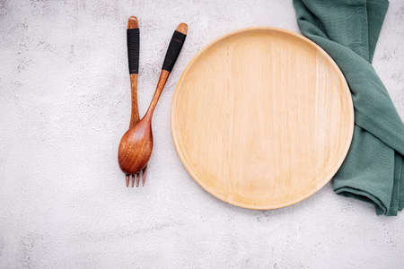 Food conceptual image of wooden plate with spoon and fork on white concrete background.
