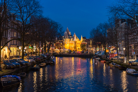 Houses in Amsterdam, traditional old flemish buildings and boats at night in Amsterdam on Amstel river and canals, Netherlands