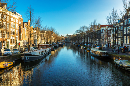 residential construction: Beautiful view of Amsterdam canals with bridges and typical flemish houses in sunny weather with blue sky.