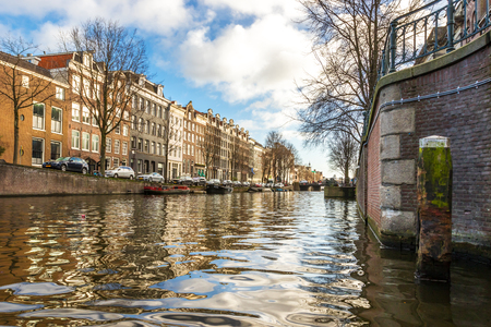 Beautiful view of Amsterdam canals with bridges and typical flemish houses in sunny weather with blue sky.