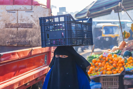 Woman in niqab carries a box on her head with vegetables, egyptian people on street