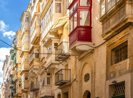 Typical narrow maltese streets with colorful traditional windows and wooden shutters and balconies, clear blue sky on a summer day, Valletta, Malta